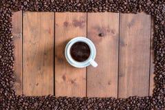 顶视图咖啡与咖啡豆方形的框架的在木 库存照片