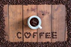 顶视图咖啡与咖啡豆方形的框架的在木 库存图片