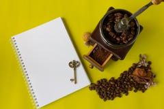 顶视图咖啡豆、grinded豆在葡萄酒木磨咖啡器,空白的书和钥匙在黄色背景 免版税库存照片
