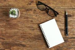 顶视图图象杯有笔的开放笔记本在木桌上 免版税库存照片