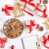 顶视图圣诞节与礼物的假日构成在与红色缎丝带、装饰、手表和笔记本的工艺纸在白色wo 库存图片