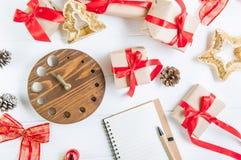 顶视图圣诞节与礼物的假日构成在与红色缎丝带、装饰、手表和笔记本的工艺纸在白色wo 库存照片