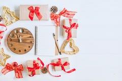 顶视图圣诞节与礼物的假日构成在与红色缎丝带、装饰、手表和笔记本的工艺纸在白色wo 免版税库存图片