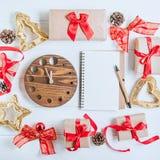 顶视图圣诞节与礼物的假日构成在与红色缎丝带、装饰、手表和笔记本的工艺纸在白色wo 免版税库存照片