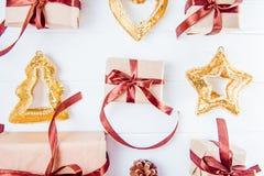 顶视图圣诞节与礼物的假日构成在与缎丝带和装饰的工艺纸排行了在白色木backg的行 免版税库存照片