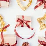 顶视图圣诞节与礼物的假日构成在与缎丝带和装饰的工艺纸排行了在白色木backg的行 图库摄影