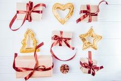 顶视图圣诞节与礼物的假日构成在与缎丝带和装饰的工艺纸排行了在白色木backg的行 库存照片
