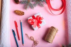 顶视图圣诞节礼物做 在桃红色桌背景的当前箱子和制作装饰 免版税图库摄影