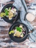 顶视图在一个黑暗的碗的新鲜蔬菜沙拉 沙拉用萝卜、红叶卷心菜、黄瓜、pesto和芝麻 图库摄影