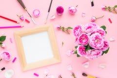 顶视图在木制框架的帆布空白,艺术材料-在的色的铅笔、刷子,树胶水彩画颜料,淡色和午后茶会玫瑰花束 免版税图库摄影