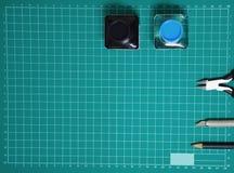 顶视图塑料式样工具箱墨水,艺术刀子,切开在削减板材和拷贝空间的钳子 库存图片