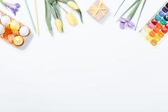 顶视图复活节构成:花、色的鸡蛋和waterc 图库摄影