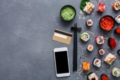 顶视图套寿司卷和gunkan近的电话和在土气灰色和米背景的信用卡 图库摄影