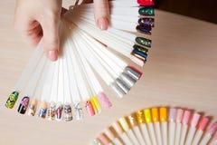 顶视图妇女选择黄色颜色紫胶指甲油 钉子技术员在美容院显示钉子服务色板显示  库存照片