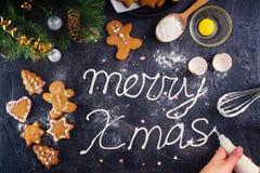 顶视图妇女递做蛋白甜饼奶油色在上写字的圣诞快乐在与ingrediens和装饰的黑石背景 库存图片