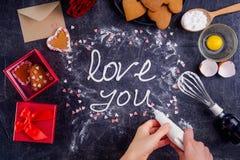顶视图妇女递做蛋白甜饼奶油色字法爱您在与成份、礼物盒和装饰d的黑石背景 免版税库存图片