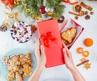 顶视图妇女递拿着从红色礼物盒的盖子用手工制造传统圣诞节姜饼人曲奇饼 白色木 免版税图库摄影