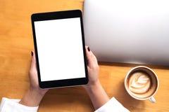 顶视图妇女` s的大模型图象递拿着有白色黑屏和膝上型计算机的,在木桌上的咖啡杯黑片剂个人计算机 免版税图库摄影