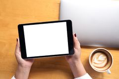 顶视图妇女` s的大模型图象递拿着有白色黑屏和膝上型计算机的,在木桌上的咖啡杯黑片剂个人计算机 免版税库存图片