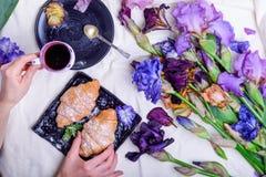 顶视图少妇吃早餐用甜新月形面包和咖啡在黑色的盘子围拢与虹膜花在床 好morni 免版税库存照片