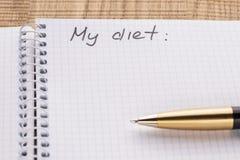 顶视图工作场所笔记本和笔在木桌背景,减速火箭的作用 题字-我的饮食 库存照片