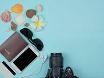 顶视图巧妙的电话,护照,太阳镜,信用卡,照相机,与在天蓝色背景的拷贝空间 库存照片