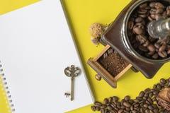顶视图平的层数咖啡行家生活方式集合、咖啡豆、碎豆在葡萄酒木磨咖啡器,空白的书和vi 免版税库存图片