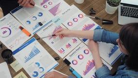 顶视图年轻业务经理在办公室分析文件,新的起始的项目的计划 股票录像