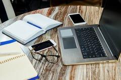 顶视图开放笔记本、膝上型计算机和玻璃在办公室桌上 3d例证图象办公室工作场所 免版税库存照片
