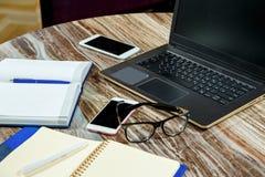 顶视图开放笔记本、膝上型计算机和玻璃在办公室桌上 3d例证图象办公室工作场所 免版税库存图片