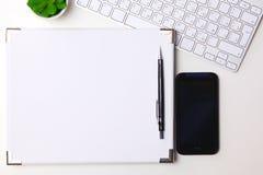 顶视图开放笔记本、铅笔和植物盆在白色书桌背景 库存图片
