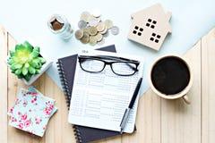 顶视图或储蓄存款存款簿平的位置或财政决算,木屋模型和硬币在办公桌桌上 免版税库存照片