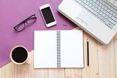 顶视图或办公室桌与空白的笔记本、智能手机、计算机膝上型计算机和咖啡的书桌工作区平的位置  免版税库存照片