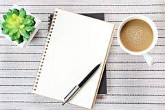 顶视图或开放笔记本的平的位置图象有空白页和咖啡杯的在桌背景,为增加准备或嘲笑  库存照片