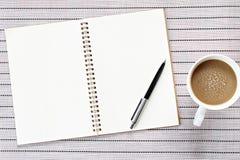 顶视图或开放笔记本的平的位置图象有空白页和咖啡杯的在桌背景 免版税库存照片