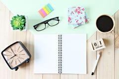 顶视图或开放笔记本纸、辅助部件、立方体日历和咖啡杯平的位置在木背景 免版税库存照片