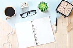 顶视图或开放笔记本纸、辅助部件、立方体日历和咖啡杯平的位置在木背景 免版税图库摄影