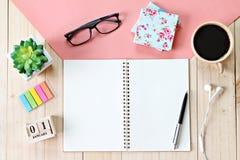 顶视图或开放笔记本纸、辅助部件、立方体日历和咖啡杯平的位置在木背景 免版税库存图片