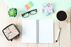 顶视图或开放笔记本纸平的位置与空白页、辅助部件和咖啡杯的在木背景 免版税图库摄影