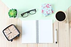 顶视图或开放笔记本纸平的位置与空白页、辅助部件和咖啡杯的在木背景 免版税库存照片