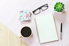 顶视图或开放笔记本纸平的位置与空白页、辅助部件和咖啡杯的在木背景 图库摄影