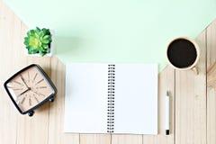 顶视图或开放笔记本纸平的位置与空白页、辅助部件和咖啡杯的在木背景,为增加准备或 库存图片