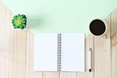 顶视图或开放笔记本纸平的位置与空白页和咖啡杯的在木背景,为增加准备或嘲笑  免版税库存图片
