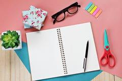 顶视图或开放笔记本纸平的位置与空白页和辅助部件的在木背景 库存图片