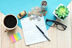 顶视图或微型汽车模型平的位置、储蓄存款书或者财政决算和硬币在办公桌桌上 免版税库存图片