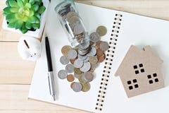 顶视图或木屋模型、硬币、开放笔记本纸和存钱罐平的位置在办公桌桌上 免版税库存照片