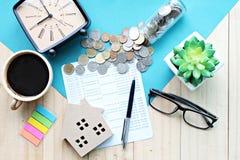 顶视图或木屋模型平的位置、储蓄存款书或者财政决算和硬币在办公桌桌上 免版税库存图片