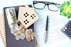顶视图或木屋模型平的位置、储蓄存款书或者财政决算和硬币在办公桌桌上 免版税图库摄影