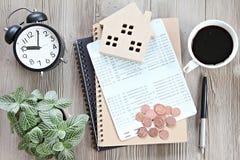 顶视图或木屋模型平的位置、储蓄帐户书或者财政决算和硬币在办公桌桌上 免版税库存照片