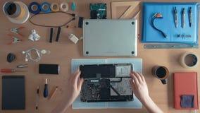 顶视图技术员工程师修理在供应和设备围拢的他的书桌上的便携式计算机 股票视频